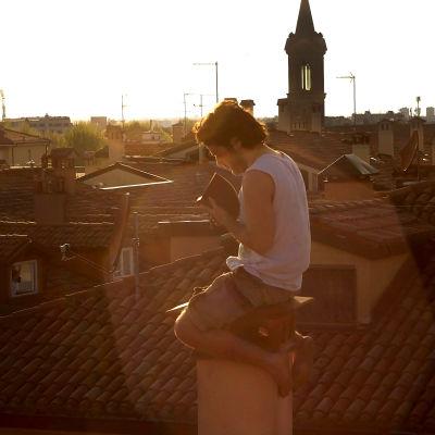 Italienska studenten Pierpaolo Mazzurco läser på taket till studentlägenheten i Bologna under coronakarantänen.