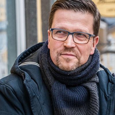 Klaus Härö sitter på en bänk och tittar ut ur bilden
