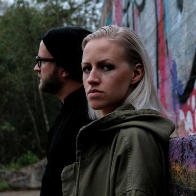 Vaaleahiuksinen nainen katsoo kameraan tuima ilme kasvoillaan, taaempana silmälasi- ja pipopäinen mies katsoo sivulle. He seisovat metsässä graffitiseinän edessä.