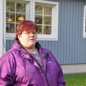 kvinna med kort rött hår och glasögon står utanförö sitt blåa egnahemshus.