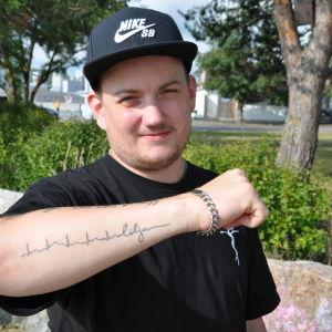 Kim Lindström håller upp sin högra arm, på den ser man tatueringen.