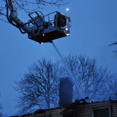 Brandmän sprutar vatten från skylift