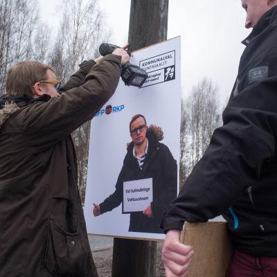 Filip Björklöf (SFP) och Eddie Lindbom (SFP) hänger up valplakat i Karis inför kommunalvalet 2017.
