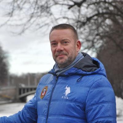 Stefan Wallin står på Biblioteksbron i Åbo och tittar in i kameran.