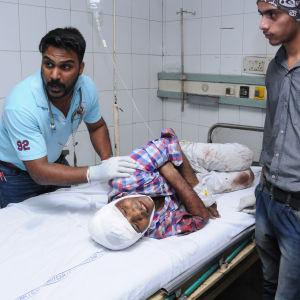 En skadad man med bandage runt huvudet ligger på en sjukhussäng, medan sjukvårdspersonal jobbar runt honom.
