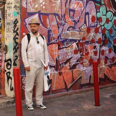 Olli Haapakangas seisoo graffitiseinän edessä.