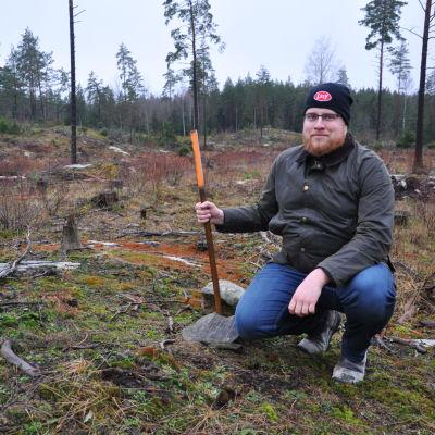 Kim sitter på huk i skogen bredvid en pinne som visar var ladugården ska byggas.