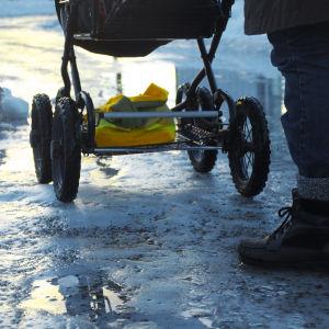 En person skuffar fram en barnvagn på en isig väg.