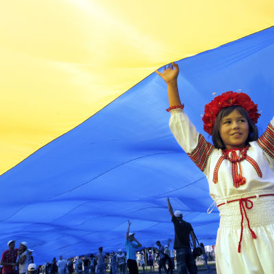 Ukrainsk flicka i folkdräkt håller fupp landets flagga under självständighetsdagen 24.8.2012