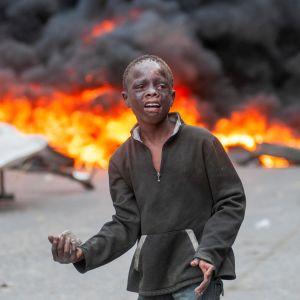 En ung pojke som deltog i stenkastningen under söndagens protester i Port-au-Prince.