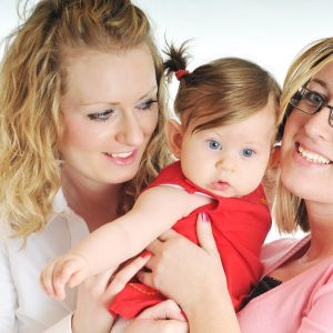 En regnbågsfamilj med två mammor håller i sin lilla dotter.