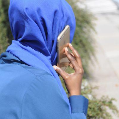 Muslimsk kvinna talar i mobiltelefon.