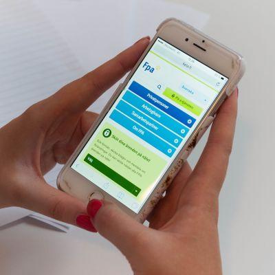Någon med rödlackade naglar håller i en smarttelefon. På skärmen syns FPA:s hemsida.