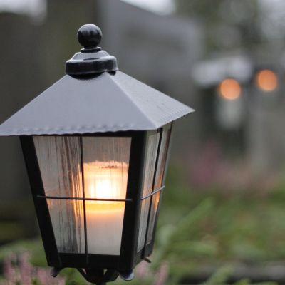 En lykta med ett brinnande ljus vid en grav.