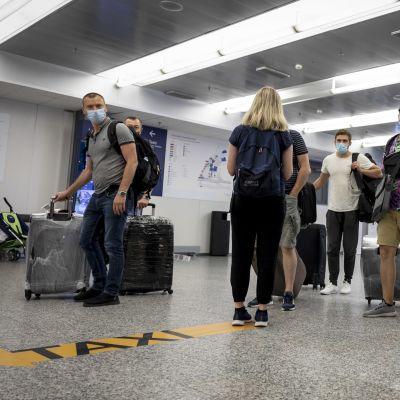 Matkustajia Helsinki-Vantaan lentoaseman saapuvien aulassa.