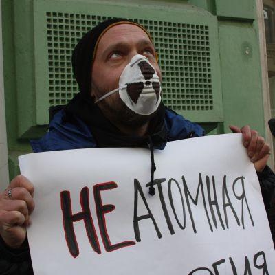 En man i munskydd håller ett ryskspråkigt plakat.
