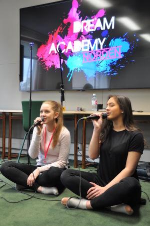 två tjejer från Kaustisen musiikkilukio sitter på golvet och sjunger i microfon