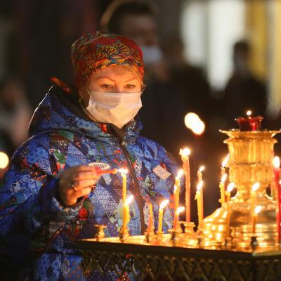 En kvinna i munskydd tänder ljus i kyrka under påsk.