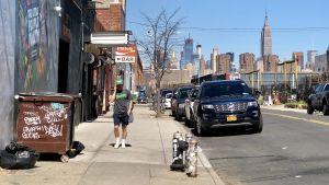 Utsikten från Brooklyn mot Manhattans skyskrapor. Vårdag i värmen. Man i shorts passerar graffitiklottrad soptunna