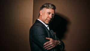 Näyttelijä Mikael Persbrandt nojaa seinään, kädet sylissä, katsoo suoraa kameraan.