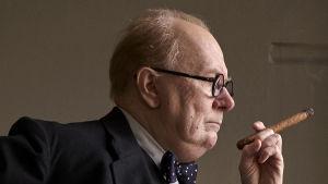Närbild på Winston Churchill (Gary Oldman) i profil med cigarr i handen.