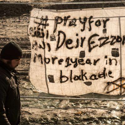 """Banderoll i flyktinglägret i Calais med texten """"Be för Deir Ezzor, belägrat i över ett år"""""""