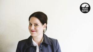 lastenpsykiatrian erikoislääkäri ja perheterapeutti Janna Rantala hymyilee kameralle valkoista taustaa vasten.