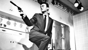 Mies pistoolin kanssa mustavalkoisessa kuvassa.