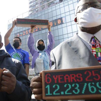"""Ihmiset pitävät käsissään näyttöjä, joissa teksti """"kuusi vuotta, 256 päivää"""", taustalla samat tiedot näytöllä rakennuksen seinällä"""