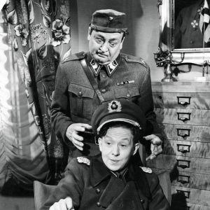 Ylivääpeli (Pentti Viljanen) on aikeissa käydä kenraaliksi pukeutuneen alokkaan (Lasse Pöysti) kimppuun.