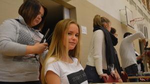 Frisörstuderande Fanny Dahlqvist fixar gmnasiestuderande Ronja Dufholms hår under flickornas dag i Ekenäs högstadieskola