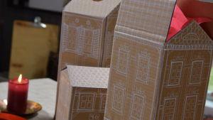 Tre pepparkakshus gjorda av brun kartong och dekorerade med vit tusch. Bredvid står ett tänt ljus och ett fat med pepparkakor.