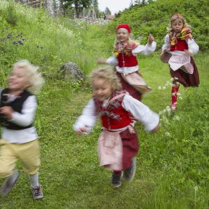 Barn som springer i folkdräkter.