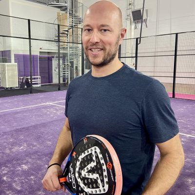 Arto Lahtinen pitää padel-mailaa käsissään pelikentällä.