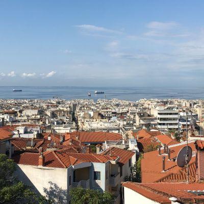 Vy över takåsarna i Thessaloniki där det syns tegelpannor på ljusa hus och på redden ligger några lastfartyg.