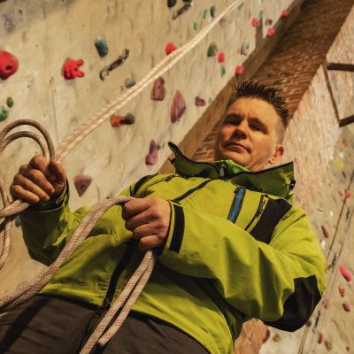 Mies neonvihreässä takissa pitelee käsissään narua. Taustalla kiipeilyseinä.