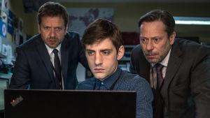 Kolme miestä tuijottaa tietokoneen ruutua