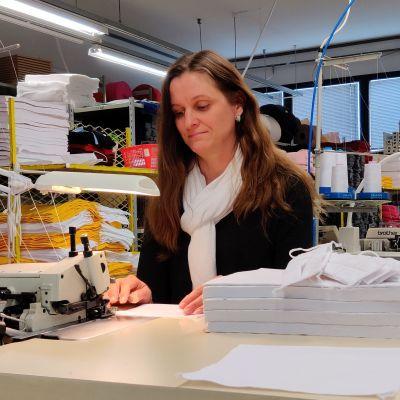 Husky Oy:n toimitusjohtaja Marjo Kuparinen ompelukoneen ääressä valmistamassa kasvomaskia.