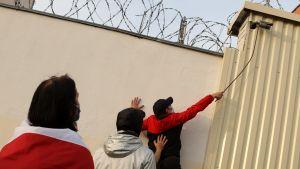 Demonstration till stöd för politiska fångar i Belarus 4.1.0.2020. Demonstranter försöker avlägsna en bevakningskamera