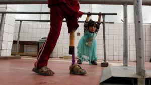 I förgrunden kan man se ett barn med ett protesben. I bakgrunden en liten flicka i ljusblå klänning.
