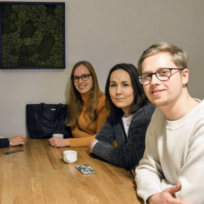 Studerande sitter vid ett bord och ser i kameran.