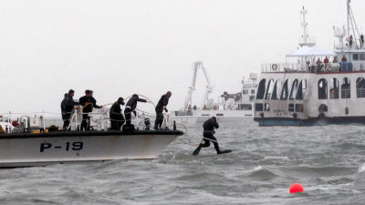 Dykare hoppar i vattnet vid olycksplatsen.