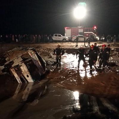 En bild på ett översvämmat område, en bil ligger på sida.
