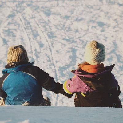 Lapset laskevat talvella mäkeä.