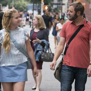 Renée och Ethan promenerar i stadsvimlet.