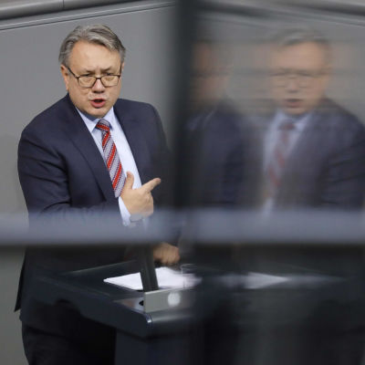 Den bayerske CSU-politikern Georg Nüsslein står och pratar och pekar i en talarstol. En suddig variant av honom speglas i en skärm.