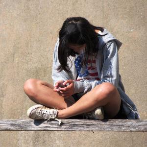 Flicka sitter med nedböjt huvud.
