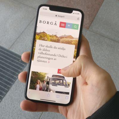 En användare surfar på Borgå stads webbplats via mobilen.
