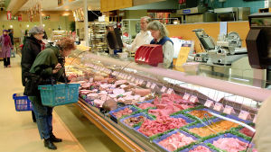 Asiakkaita ja myyjiä ruokakaupan lihatiskillä.