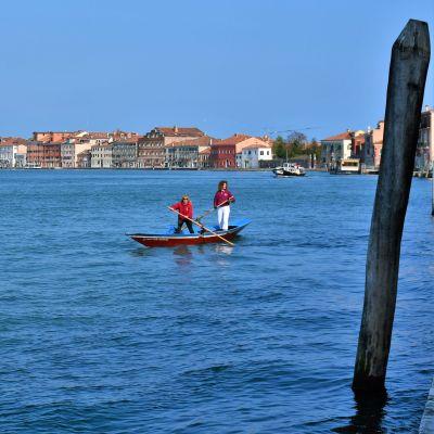 Två kvinnor står i en båt och paddlar sig fram på ett azurblått hav med Vendig i silhuett i bakgrunden.